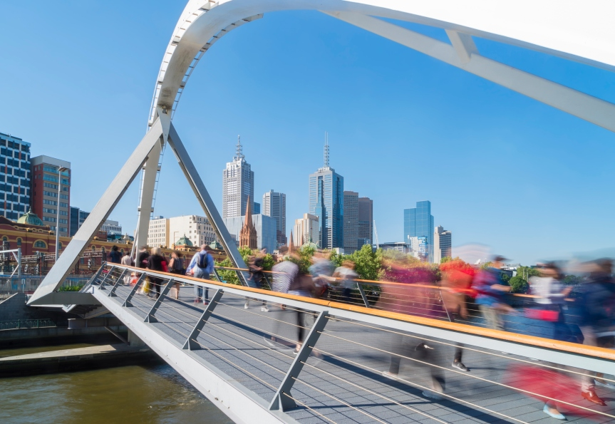 People walking across the Southgate footbridge in Melbourne